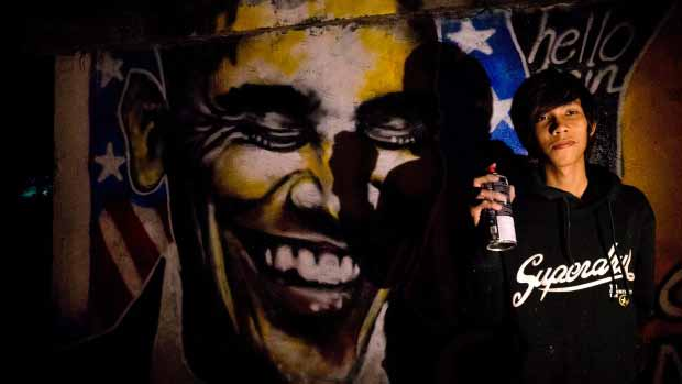 Artist Arker Kyaw poses with the graffiti welcoming U.S. President Barack Obama in Yangon, Myanmar, at dawn on Saturday, Nov. 17, When Arker Kyaw heard Obama was coming to Myanmar, he gathered 15 cans of spray paint and headed for a blank brick wall under cover of darkness. Kyaw, whose passion is graffiti, labored from 3 am until the sun came up. photo: gemunu amarasinghe