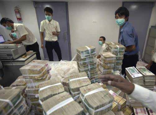 Employees count and pack money inside a bank in Yangon | photo : reuters/ minzayar