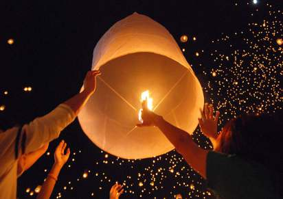 LETTING A KHOM LOI FLOAT INTO THE AIR AT THE YI PENG FESTIVAL