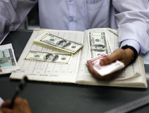 A man counts US dollars and Myanmar kyats at a money changer in Ynagon March 21, 2012. Photo: Reuters, ivcpost.com