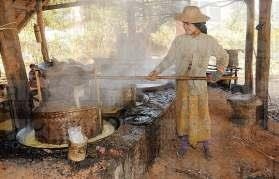 SMALL RURAL SUGAR FACTORY, A WOMAN CONCENTRATING SQUEEZED SUGAR CANE JUICE, KAUNGDAING, INLE