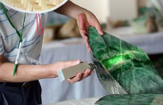 A CUSTOMER CHECKS THE QUALITY OF JADE AT AN AUCTION IN YANGON