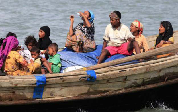 ROHINGYA PEOPLE ON A BOAT CROSSING THE RIVER FROM MYANMAR INTO BANGLADESH