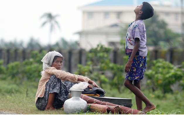ROHINGYA PEOPLE REST BY THE ROAD WITH THEIR BELONGINGS AS THEY MOVE FROM THEIR VILLAGE AFTER RECENT VIOLENCE IN SITTWE