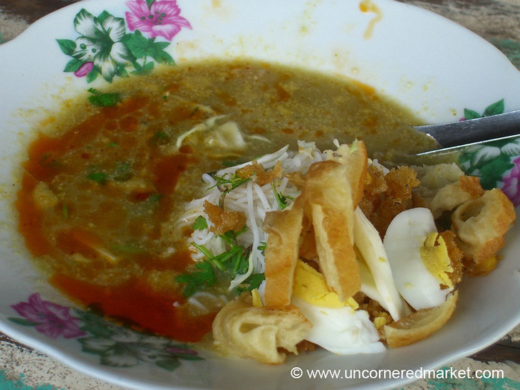 A delicious breakfast soup in Meiktila, Burma (Myanmar) of fresh rice noodles, a light coconut milk broth, tofu, and egg - all topped with fresh herbs.