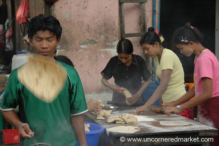 The line of women roll out the dough while the men cook and flip the chapatis at the Chapati Stand on the corner of 82nd and 27th Streets in Mandalay, Burma (Myanmar).