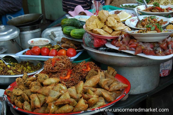 Samosas, fried noodles, shrimp, tofu, chickpeas and fresh vegetables make up a street food stand in Rangoon, Burma (Yangon, Myanmar).