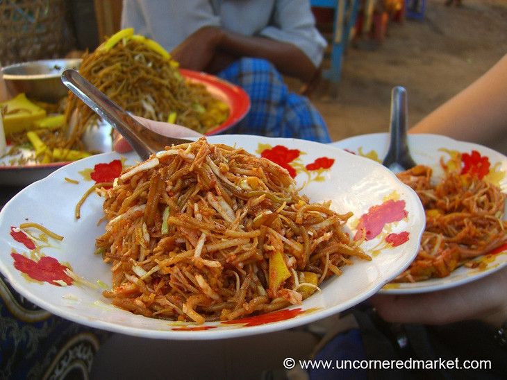 Enjoying a light lunch of cold noodles at the market.  Tasty, spicy and criminally cheap...Taken in Bago, Burma (Myanmar).