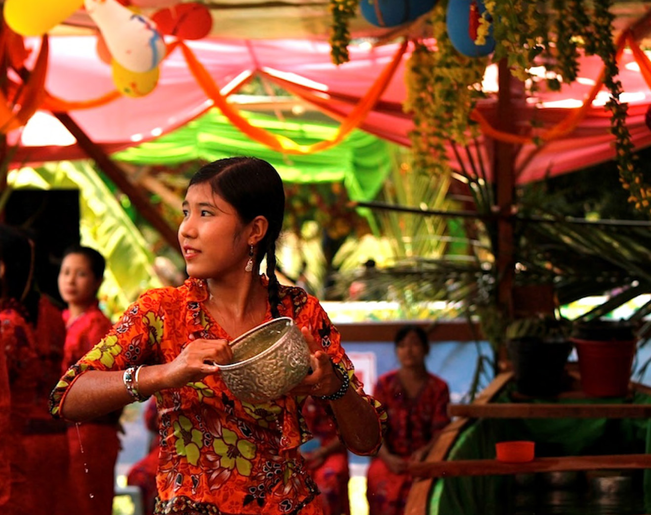 A GIRL DRESSED IN TRADITIONAL RAKHINE DRESS POURS WATER AT REVELERS DURING THINGYAN